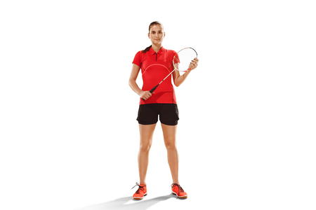 Young woman badminton player over white studio background. Fit female athlete isolated on white.