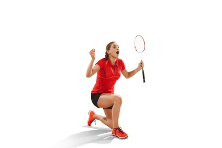 Young woman after playing badminton standing as winner over white studio background. Fit female athlete isolated on white. Victory concept Stock Photo