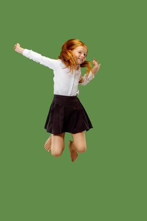 Young happy caucasian teen girl jumping in the air, isolated on green studio background. Beautiful female half-length portrait. Human emotions, facial expression concept.