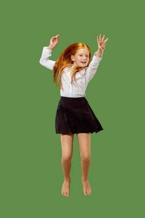 f14448eed92e4 Young happy caucasian teen girl jumping in the air, isolated on green  studio background.