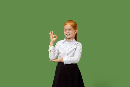 Happy teen girl standing, smiling and pointing to himself isolated on trendy green studio background. Beautiful female half-length portrait. Human emotions, facial expression concept. Standard-Bild