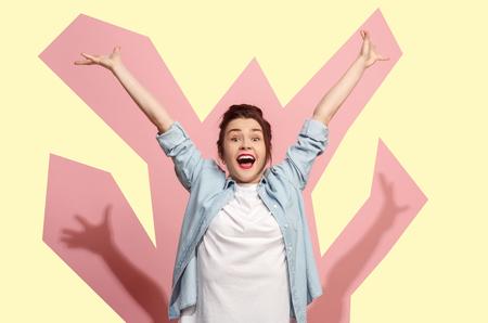 Gané. Ganar éxito mujer feliz celebrando ser un ganador. Imagen dinámica del modelo de mujer caucásica sobre fondo rosa de estudio. Victoria, concepto de deleite. Concepto de emociones faciales humanas. Colores de moda