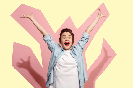 I won. Winning success happy woman celebrating being a winner. Dynamic image of caucasian female model on pink studio background. Victory, delight concept. Human facial emotions concept. Trendy colors