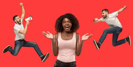 Wauw. Prachtige vrouwelijke halve lengte portret geïsoleerd op rode studio achtergrondgeluid. Jonge verrast vrouw en springende lopende man geïsoleerd op rood. Menselijke emoties, gezichtsuitdrukking concept. Trendy kleuren