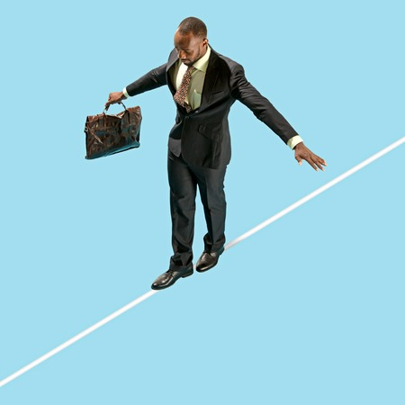 Business man on tightrope concentrate to walking isolated on blue background. Business, career, risk concepts
