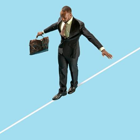 Geschäftsmann auf Gratwanderung konzentrieren sich auf das Gehen lokalisiert auf blauem Hintergrund. Geschäfts-, Karriere-, Risikokonzepte