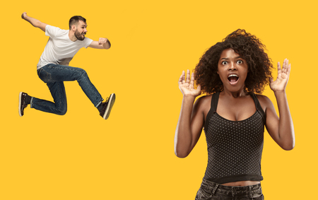 Wow. Beautiful female half-length portrait isolated on gold studio backgroud. Young surprised woman and jumping running man isolated on yellow. Human emotions, facial expression concept. Trendy colors