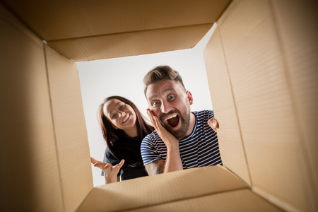 The surprised man and woman unpacking, opening carton box and looking inside. The package, delivery, surprise, gift lifestyle concept Фото со стока