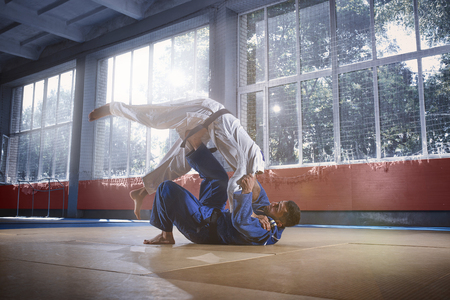 Two judo fighters showing technical skill while practicing martial arts in a fight club. The two fit men in uniform. fight, karate, training, arts, athlete, competition concept Archivio Fotografico