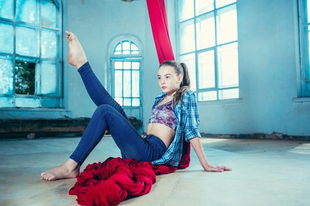 Graceful gymnast resting after performing aerial exercise with red fabrics on blue old loft background. Young teen caucasian fit girl. The circus, acrobatic, acrobat, performer, sport, fitness, gymnastic concept 免版税图像