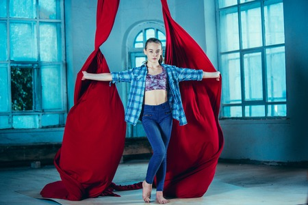 Graceful gymnast resting after performing aerial exercise with red fabrics on blue old loft background. Young teen caucasian fit girl. The circus, acrobatic, acrobat, performer, sport, fitness, gymnastic concept Stock Photo