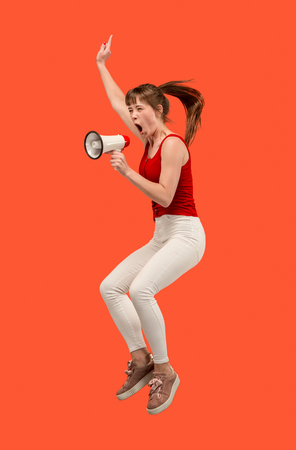Beautiful young woman jumping with megaphone isolated over red background. Runnin girl in motion or movement. Human emotions and facial expressions concept
