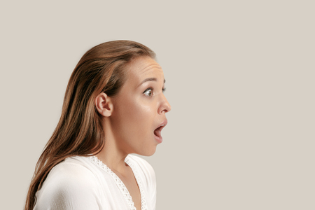 Guau. Retrato de perfil de medio cuerpo femenino hermoso aislado sobre fondo gris de estudio. Joven mujer emocional sorprendida de pie con la boca abierta. Las emociones humanas, el concepto de expresión facial.
