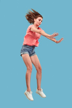 Freedom in moving. Mid-air shot of pretty happy young woman jumping and gesturing reject against blue studio background. Runnin girl in motion or movement. Human emotions and facial expressions concept Stock Photo