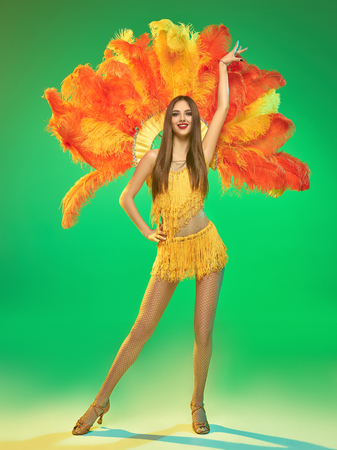 young beautiful dancer with carnival feather and fringe posing on studio background 版權商用圖片 - 106539585