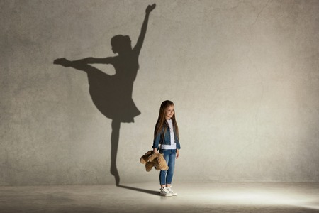 Baby girl dreaming about dancing ballet. Childhood and dream concept. Conceptual image with shadow of ballerina on the studio wall Banco de Imagens - 106633018