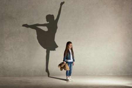 Niña soñando con bailar ballet. Concepto de infancia y sueño. Imagen conceptual con sombra de bailarina en la pared del estudio