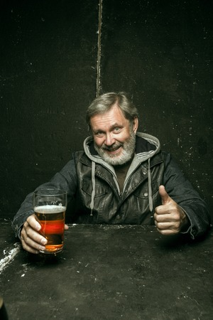 Smiling bearded man drinking alcohol in pub. Enjoying my favorite beer. The front view of handsome smiling senior man with glass of beer sitting at the wooden table. Studio shot with caucasian model