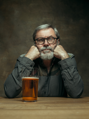 Sad bearded man drinking alcohol in pub. Enjoying my favorite beer. The front view of handsome smiling senior man with glass of beer sitting at the wooden table. Studio shot with caucasian model
