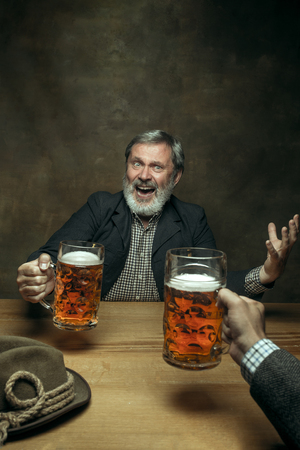 Smiling bearded man clinking with mug of alcohol in pub. Enjoying my favorite beer. The front view of handsome smiling senior man with glass of beer sitting at the wooden table. Studio shot with caucasian model