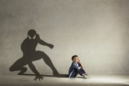 The little boy dreaming about hero figure with muscles. Childhood and dream concept. Conceptual image with boy and shadow of fit athlete on the studio wall Foto de archivo