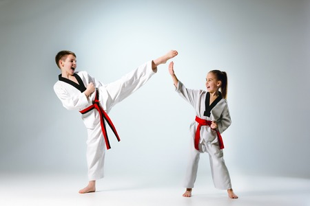 The studio shot of group of kids training karate martial arts on gray backlground Imagens