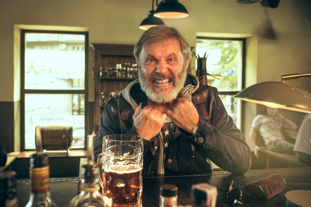 Senior bearded man drinking alcohol in pub and watching a sport program on TV. Enjoying my favorite teem and beer. Man with mug of beer sitting at table. Football or sport fan. Human emotions concept