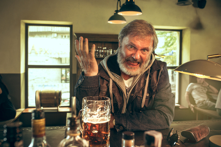 Angry bearded man drinking alcohol in pub and watching a sport program on TV. Enjoying my favorite teem and beer. Man with mug of beer sitting at table. Football or sport fan. Human emotions concept Stockfoto
