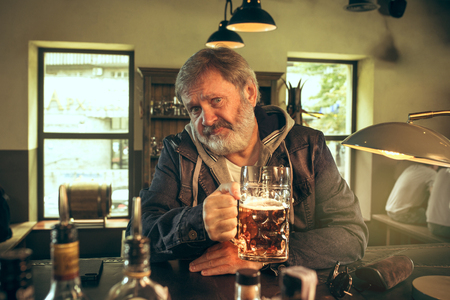 Sad senior bearded man drinking alcohol in pub and watching a sport program on TV. Enjoying my favorite teem and beer. Man with mug of beer sitting at table. Football or sport fan. Human emotions concept Stockfoto