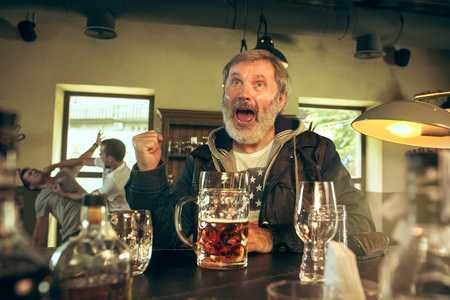 Senior bearded man drinking alcohol in pub and watching a sport program on TV.