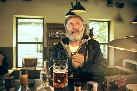 Senior begging bearded man drinking alcohol in pub and watching a sport program on TV.