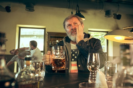 Senior bearded man drinking alcohol in pub and watching a sport program on TV. Enjoying beer. Man with mug of beer sitting at table. Football or sport fan. fight of fans in the background