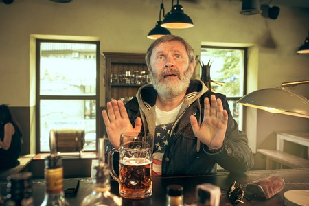 Senior begging bearded man drinking alcohol in pub and watching a sport program on TV. Enjoying my favorite teem and beer. Man with mug of beer sitting at table. Football or sport fan. Human emotions Stockfoto