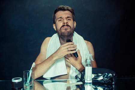 The young caucasian man in bedroom sitting in front of the mirror during scratching his beard at home. Human emotions concept. Lifestyle and skincare concepts Stock Photo