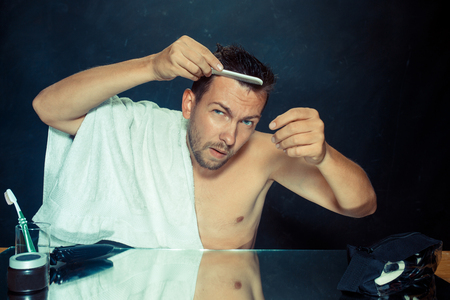 Man With Comb Concerned About Hair Loss. Close up photo of young caucasian man looking on his face. at home. Human emotions concept. Lifestyle and skincare concepts
