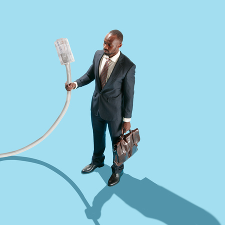 The african man holding USB cable in hand. Flat isometric view and conceptual image of businessman as IT-specialist. Office concept. Business processes, workplace concepts. Miniature people. Collage