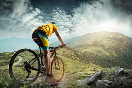 The young fit man in helmet conquering mountains on a bicycle. The bike, nature, bicycle, sport, cycle, extreme, lifestyle, adventure and sport concept Stock Photo