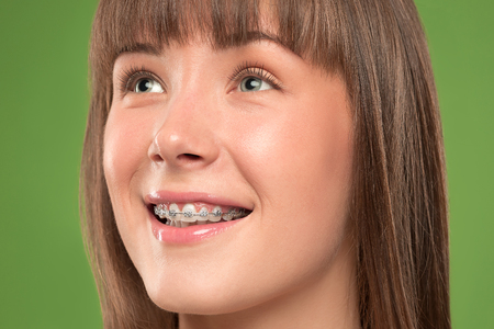 Schöne junge Frau mit Zahnspangen auf Grün