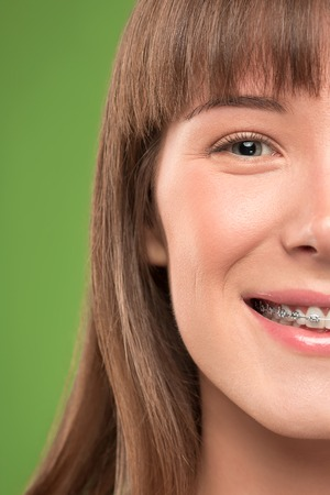 Beautiful young woman with teeth braces on green