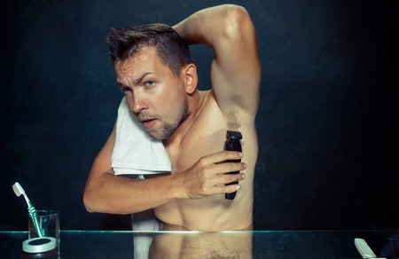 Photo of handsome man shaving his armpit. The young man in bedroom sitting in front of the mirror at home. Human skin and lifestyle concept Stock Photo