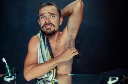 Foto des gutaussehenden Mannes, der seine Achselhöhle rasiert. Der junge Mann im Schlafzimmer sitzt zu Hause vor dem Spiegel. Konzept der menschlichen Haut und des Lebensstils Standard-Bild