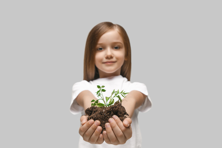 Kids hands with seedlings on studio background. Spring, plant, nature, growing and care concept. Caucasian little girl Stock Photo - 107133781
