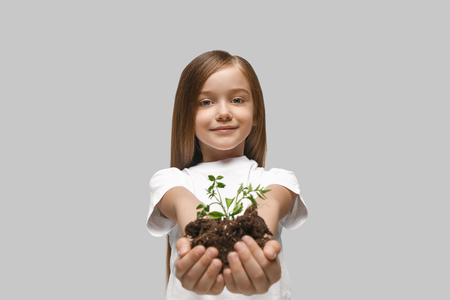 Kids hands with seedlings on studio background. Spring, plant, nature, growing and care concept. Caucasian little girl Stock Photo - 107216951