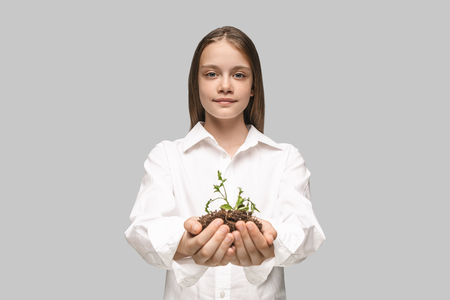 Teen hands with seedlings on studio background. Spring, plant, nature, growing and care concept. Caucasian little girl