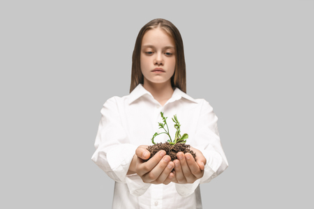 Teen hands with seedlings on studio background. Spring, plant, nature, growing and care concept. Caucasian little girl Stock Photo - 107216955