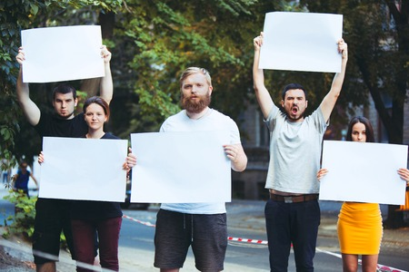 Group of protesting young people outdoors. The protest, people, demonstration, democracy, fight, rights, protesting concept. The caucasian men and womem holding empty posters or banners with copy space Stockfoto