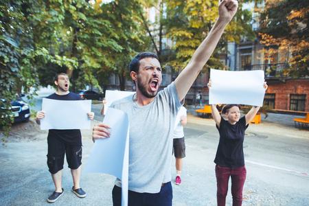 Groep protesterende jongeren buitenshuis. Het protest, de mensen, de demonstratie, de democratie, de strijd, de rechten, het protestconcept. De blanke mannen en vrouwen die lege posters of spandoeken met kopie ruimte houden Stockfoto