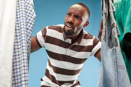 Handsome afro man with beard choosing shirt in a shop Foto de archivo - 107197052