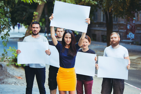 Group of protesting young people outdoors. The protest, people, demonstration, democracy, fight, rights, protesting concept. The caucasian men and womem holding empty posters or banners with copy space Фото со стока