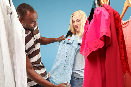 Image of pretty female girl and african man looking a dress while choosing it. Concept of shopping and lifestyle